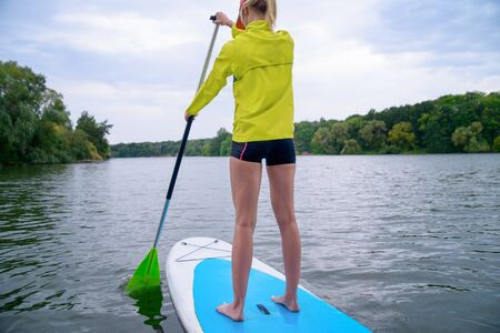 Rear view. Woman resting on the SUP board and enjoying life in the early morning on the big river