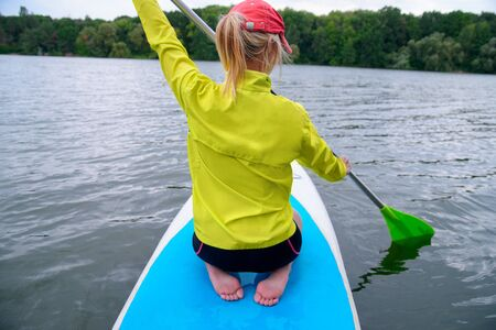 back view of a sporty girl with white hair sitting on a board with a paddle on the river