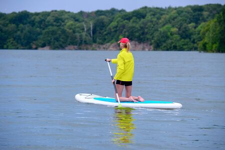SUP Stand up paddle board concept - young woman paddle boarding on a lake