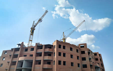 Building of a multi-storey brick house. Crane supplies construction materials to builders at a height of