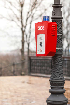 Help or police call button. SOS. A stand with a button is fixed on the street, on a lamppost. Red housing with blue warning light on top.