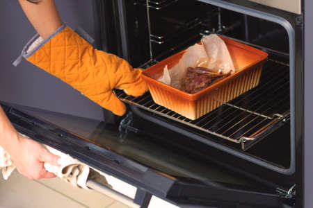 The duck meat is baked in the oven on a ceramic baking sheet. Hands of a girl put baking inside the oven.