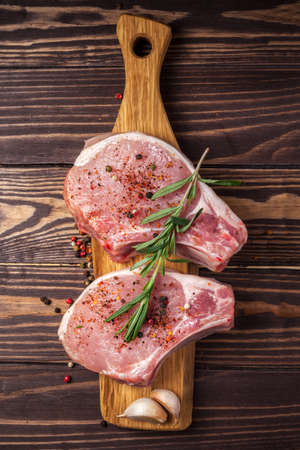 Pork steak with spices and rosemary. Juicy and fresh raw meat with peppercorns on a wooden cutting board on the kitchen worktop. vertical photo