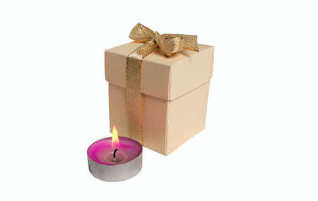 beautifully wrapped: beautifully wrapped gift with a bow next to a burning candle round Stock Photo