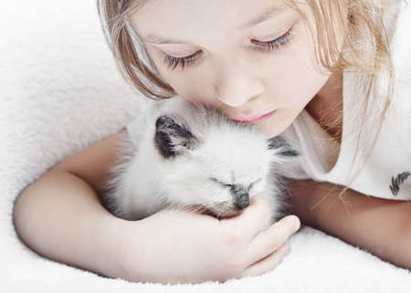 little cute girl affectionately hugging  kitten