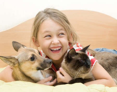 hilarity: little girl with a dog and a cat on a bed of yellow color