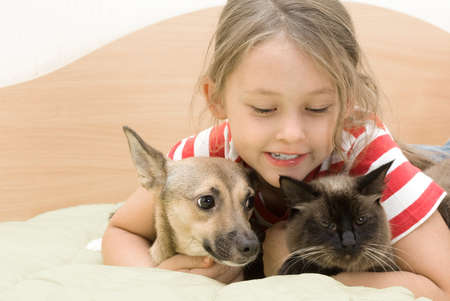 tenderly: Little girl tenderly embraces a dog and a cat