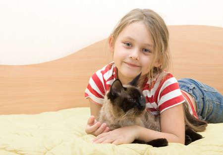 subtlety: Little girl tenderly embraces cat Stock Photo