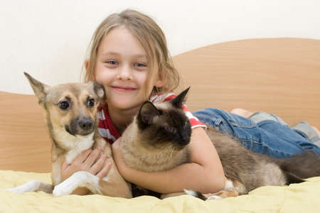 hilarity: girl with pets on a bed of yellow color