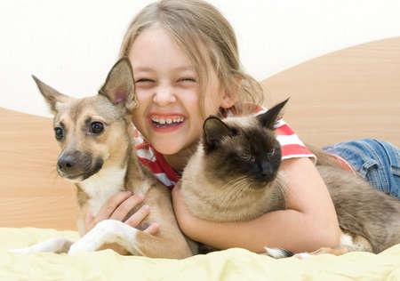 amabilidad: Muchacha de risa con las mascotas Foto de archivo