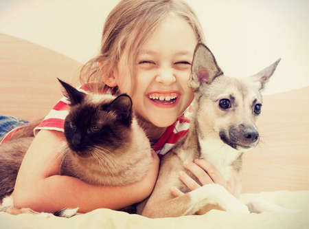 family with one child: child hugging a cat and dog