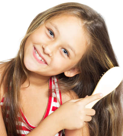 pretty smiling little girl brushing her hair isolated on white background  Stock Photo