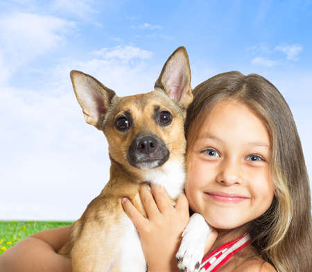 kid with a dog in her arms on a blue sky background