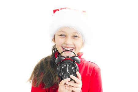little girl in Santa Claus hat holding alarm clock showing twelve oclock photo