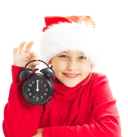 little girl in Santa Claus hat holding alarm clock showing twelve oclock photo