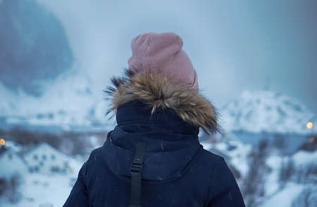 girl stands backwards and looks at the winter landscape