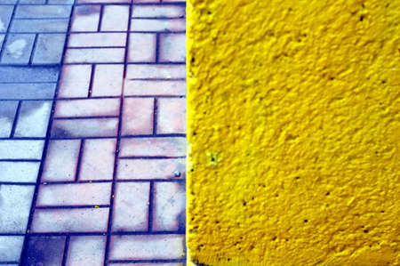 a yellow wall and paving slabs