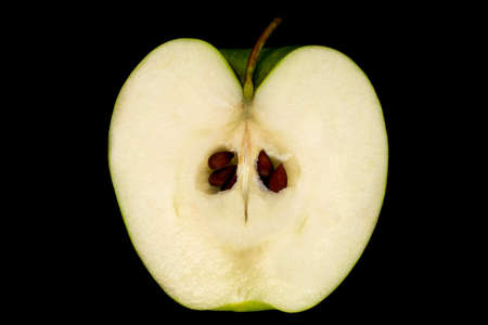 Cut green Apple with pits and peduncle on black background