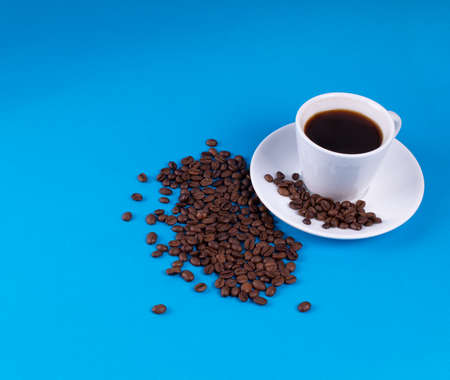 Spilled coffee grains after white mug on blue background