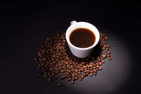 A beam of light is directed at a cup of coffee standing in a pile of coffee beans.