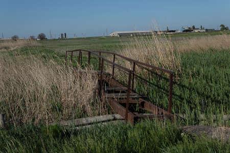 Narrow pedestrian bridge over the river is broken and abandoned