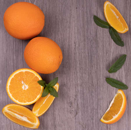 orange slices of orange with mint leaves on a wooden table in close-up
