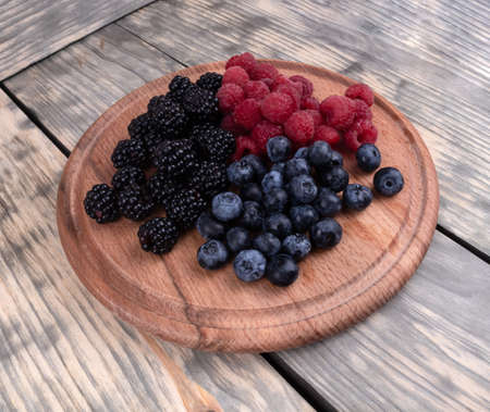 To view on a composition of summer juicy ripe berries laying in a textured wooden plate Reklamní fotografie