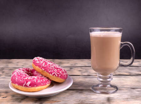 Two donuts and a cup of coffee with milk standing on wooden planks 版權商用圖片
