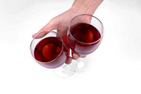 A hand holding two glasses filled with red wine on white background