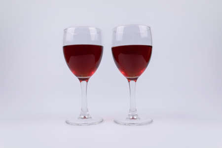 Side view of two glasses of whine standing on white background Фото со стока