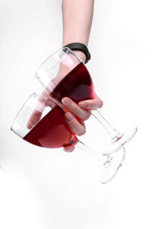 A hand with watches holding two glasses of red wine Фото со стока