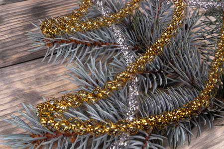 on a wooden surface on the right, a sprig of spruce with needles is highlighted in close-up. Decorated with a decorative rain