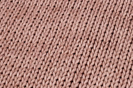 Knitted material from woolen threads of light beige color without ornaments