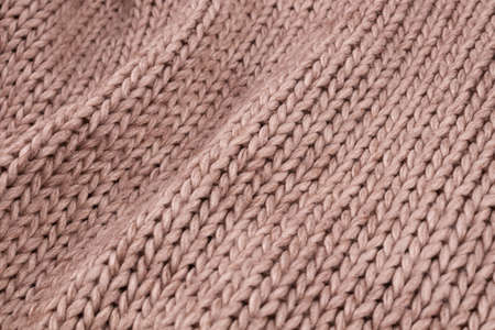 Beautiful large parallel waves of hanging beige knitted woolen fabric