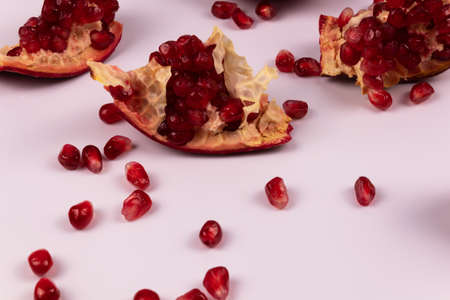 three pieces of pomegranate and peeled grains scattered around Stok Fotoğraf