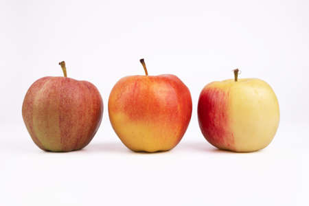 three apples of different colors lie parallel