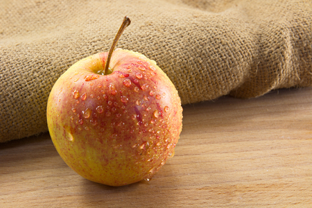 apple sack: Apple with splashing water on a wooden background and burlap