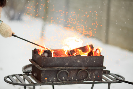 brazier: Hand with poker adjusts the coals in the brazier. Lighting the barbecue in the backyard in the winter.