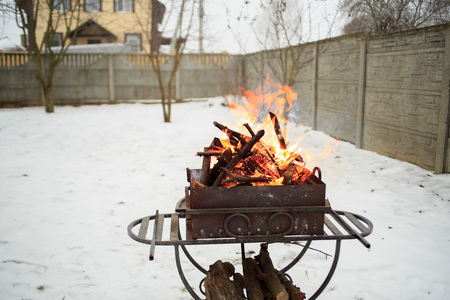 brazier: Barbecue in the backyard in the winter. Flames for background.