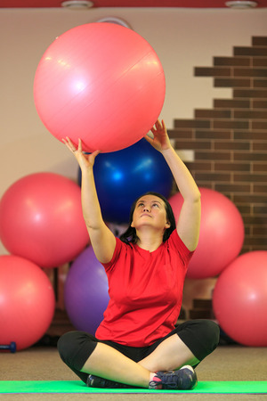 Young beautiful woman doing exercises with a fit ball at the fitness center