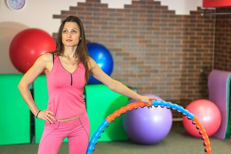 fitball: Young beautiful white girl in a pink sports suit does physical exercises with a hoop at the fitness center. Interior of fitness club for background.