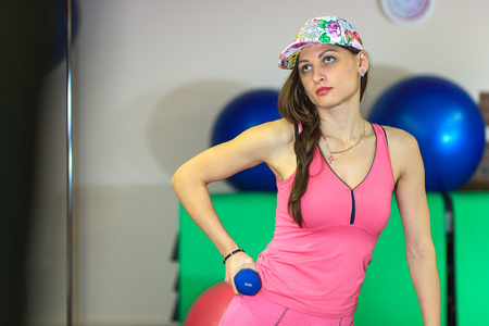 fitball: Young beautiful white girl in a pink sports suit with dumbbells stands near the step before training in a fitness club. Interior of fitness club for background. Stock Photo