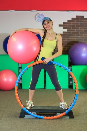 fitball: Young beautiful white girl in a yellow and gray sports suit stands with a fit ball, hoop and a dumbbell on the step at the fitness center. Interior of fitness club for background.