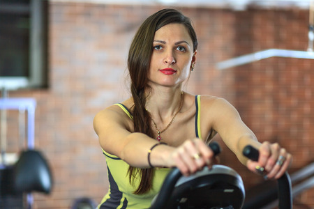 Young beautiful white girl in a yellow and gray sports suit is engaged on a stationary bike in the fitness club.