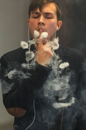 let out: Young handsome white guy let rings out of steam. Vaping.