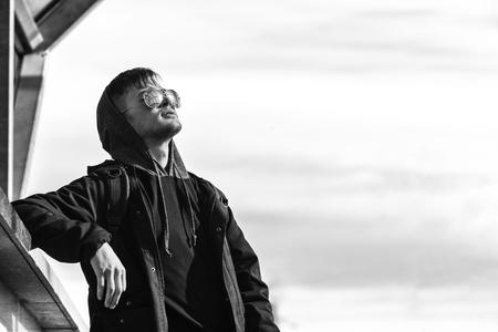 Een knappe jonge witte kerel in zonnebril en in de kap op een zonnige dag. Zwart-witfoto. Stockfoto