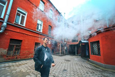 joven fumando: Vape. Un individuo blanco joven hermoso en vidrios sopla el vapor de un cigarrillo electrónico en una yarda roja vieja de la vendimia. Vaping. Foto de archivo