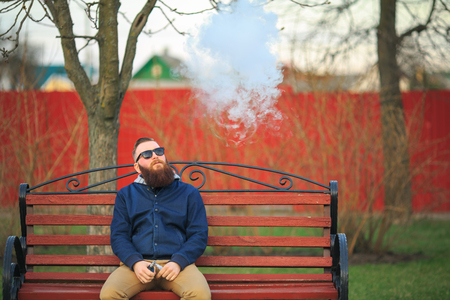 joven fumando: Vape. Young brutal man with large beard and fashionable haircut in sunglasses smokes an electronic cigarette on the red bench in the city park. Steam cloud. Lifestyle.