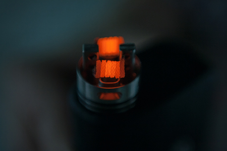 Glowing spiral of the electronic cigarette for background. Personal vaporizer. ENDS. Фото со стока