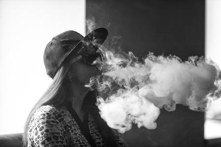 Vape. Jeune fille blanche belle dans des lunettes de soleil admet des bouffées de vapeur de la cigarette électronique. Vaping. Adolescent.